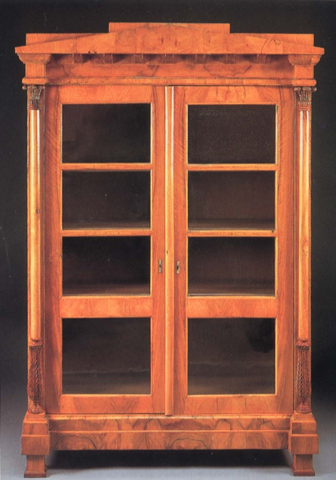 19th Century AUSTRIAN ,   Biedermeier Black Walnut Bookcase  ,  1800-1825     Walnut ,  78 x 51 5/8 x 20 1/2 in. (198.1 x 131.1 x 52.1 cm)     Peaked pediment and dentiled dornice above a pair of glazed cupboard doors opening to shelves flanked by collumnar supportw with acanthus-carved capitals and terminal raised on block feet     BIE-004-FU