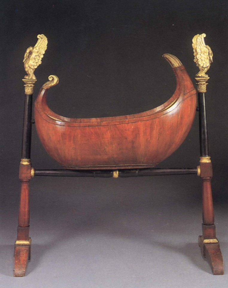19th Century AUSTRIAN ,   Biedermeier Black Walnut, Ebonized and Parcel-Gilt Cradle  ,  1800-1825     Mixed woods ,  59 1/2 x 49 1/4 x 20 1/2 in. (151.1 x 125.1 x 52.1 cm)     Rocking crib raised on ebonized columnar supports with corinthian capitals supporting later giltwood swans, the supports joined by a baluster-shaped stretcher ending in trestle legs.     BIE-003-FU