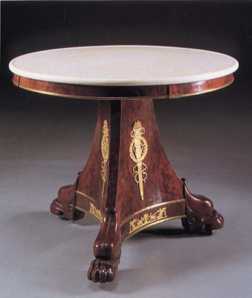 19th Century FRENCH ,   Late Empire Ormolu-Mounted Mahogany Center Table  ,  1810-1815     Mahogany ,  30 x 38 1/8 x 38 1/4 in. (76.2 x 96.8 x 97.2 cm)     Circular white mottled marble top above the plain frieze fitted with later brass border raised on a canted tripartite support fitted with ormolu flaming torches within a laurel wreath on paw feet.     FRE-003-FU